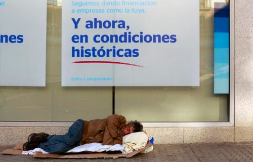 A homeless man sleeps on the pavement outside a BBVA bank branch in the Andalusian capital of Seville
