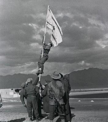 """THE INK DRAWN NATIONAL FLAG OF ISRAEL FLYING AT UM RASHRASH (EILAT) ACROSS THE GULF OF AKABA ON THE NORTHERN TIP OF THE RED SEA. äðôú ãâì äãéå áàåí øùøù, àéìú. áöéìåí, äçééì àáøäí àãï (áøï) îèôñ òì òîåã ëãé ìäðéó àú ãâì äãéå àùø àåìúø ò""""é çééìé äçèéáä."""